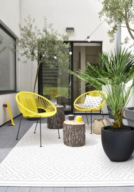 a small and bright modern terrace with yellow chairs, tree stump side tables and statement potted plants