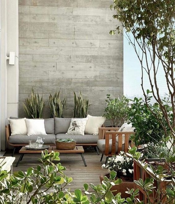 a small modern terrace with simple wooden furniture, potted plants here and there and some blooms