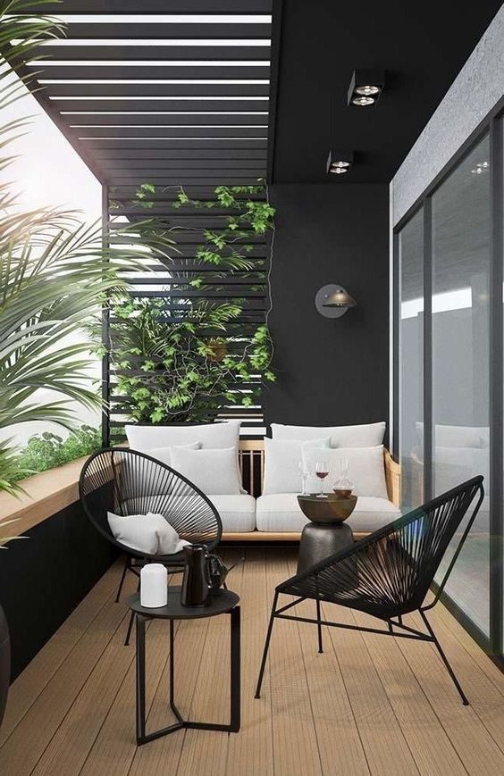 a small terrace with black wicker chairs, a comfy sofa, climbing greenery and a tiny coffee table
