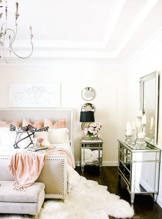 a stylish glam bedroom with an upholstered bed, mirror furniture, lamps and candles plus faux fur rugs