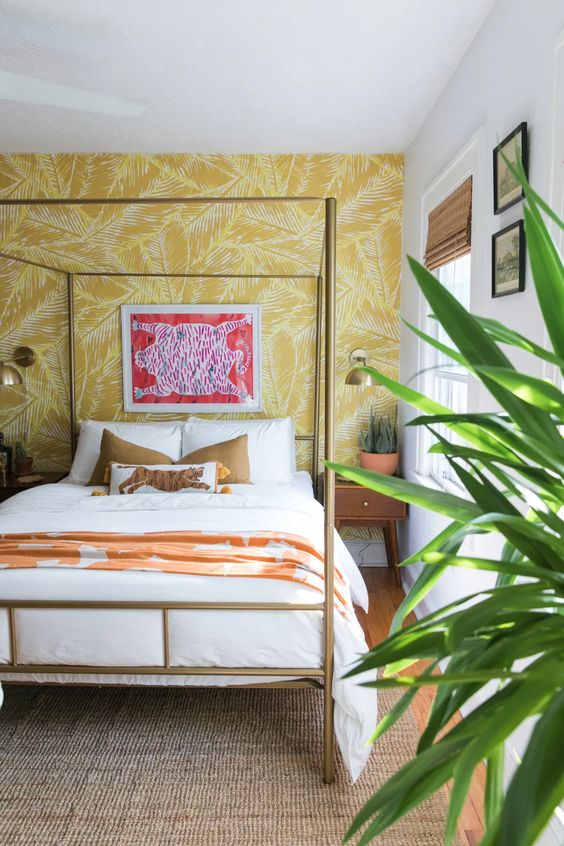 a tropical glam bedroom with a yellow printed wall, a gold bed, potted greenery, colorful pillows and textiles