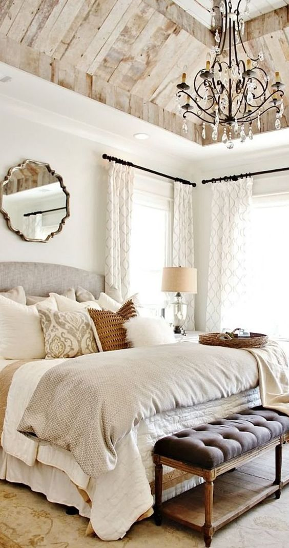 a vintage glam bedroom with a crystal chandelier, a mirror, printed textilesand lamps and candles