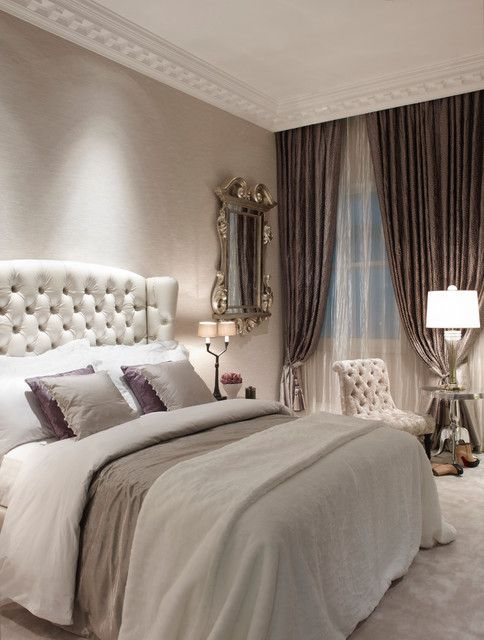 a vintage glam bedroom with a white leather bed and chair, mirror furniture, a vintage mirror and lilac touches