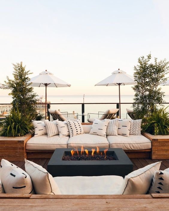 a welcoming modern terrace with comfy built-in furniture, potted plants, a fire pit in the center and a sea view