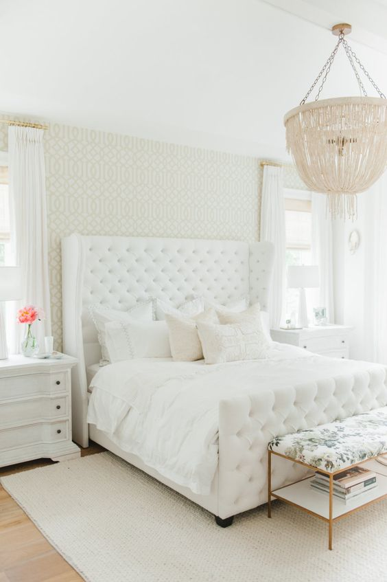 a white glam bedroom with a statement upholstered bed, white and floral furniture, a fringe chandelier