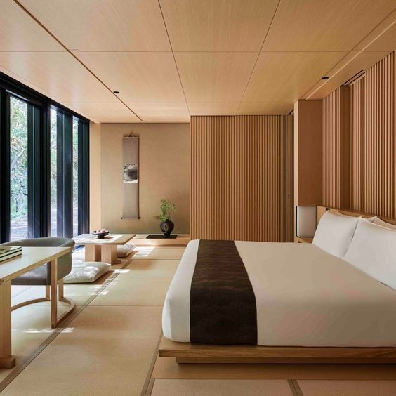 a zen bedroom with low wooden furniture, wooden screens, a glazed wall and some statement plants and artworks