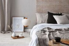a zen-like bedroom in neutrals, with a woven headboard, neutral bedding, a low wooen table and some trays plus a floor lamp