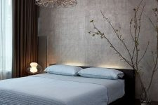 a zen-like bedroom with a silver accent wall, a dark bed with blue bedding, blooming branches and very eye-catchy lamps