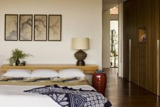 an Asian zen bedroom with a bed on the floor, a floating console at the head, a gallery wall and bright bedding