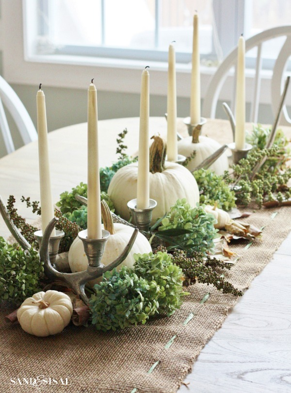 Dried hydrangea, birch bark and candelabras are a great company to white pumpkins on a natural-looking burlap table runner.