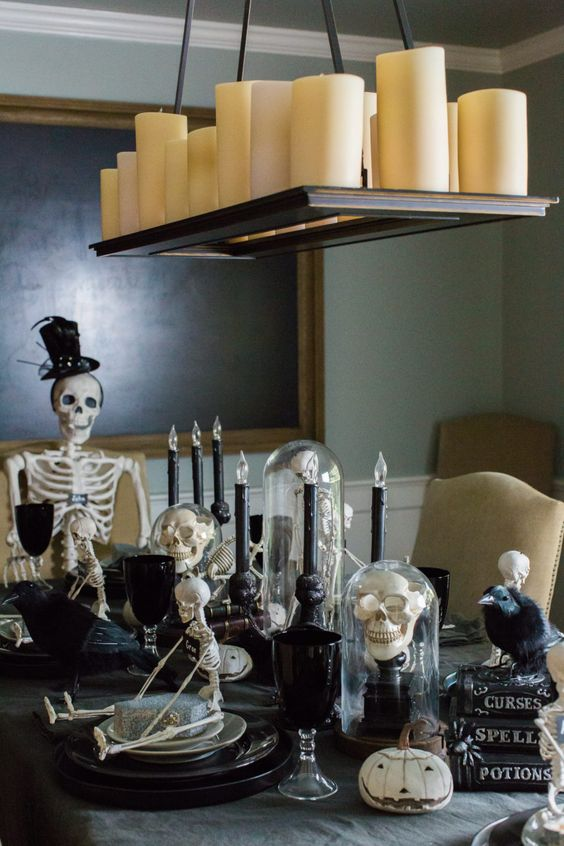 a Halloween table setting with black plates, goblets and candles, skulls and skeletons, white pumpkins