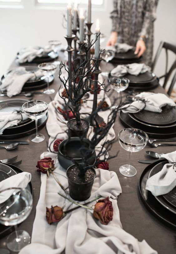 a Halloween tablescape with a white runner, dried roses, black branches, grye candles and elegant black plates