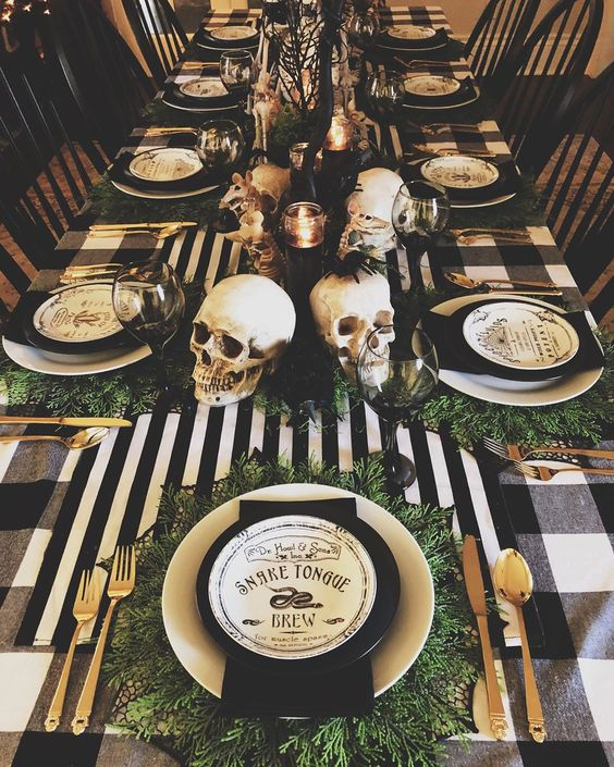 a Halloween tablescape with black and white linens, gold cutlery, skulls, candles and printed plates plus greenery