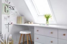 a Nordic attic home office in white, with a skylight, a built-in desk, a stool and a small gallery wall plus blooms