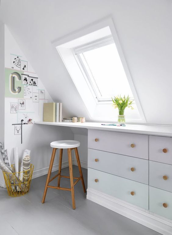 a Nordic attic home office in white, with a skylight, a built in desk, a stool and a small gallery wall plus blooms