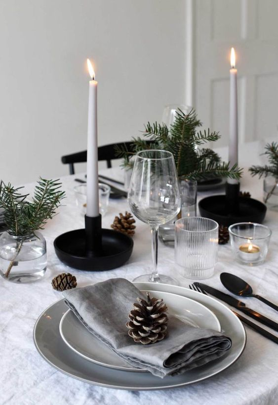 a Scandinavian winter tablescape with pinecones, evergreens, thin and tall candles and black candleholders