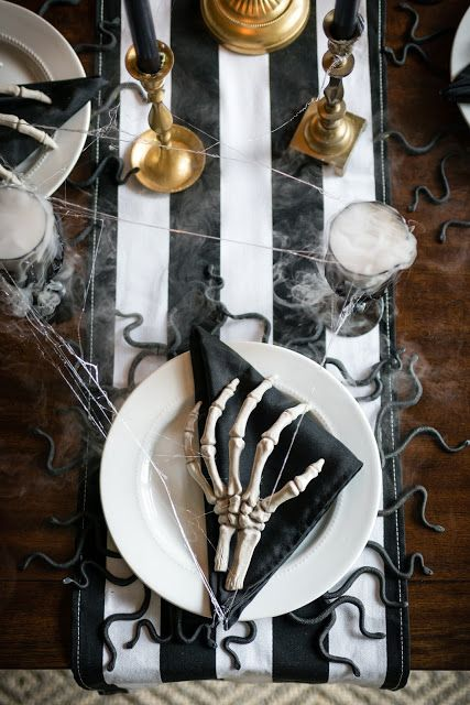 a black and white Halloween table with a striped table runner, black napkins, skeleton hands, gold candleholders and snakes