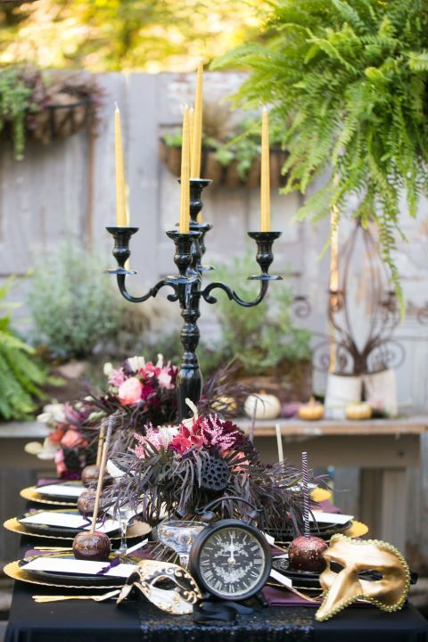a bold and refined Halloween tablescape with gold cutlery and chargers, masks, deep toned blooms and feathers and candles