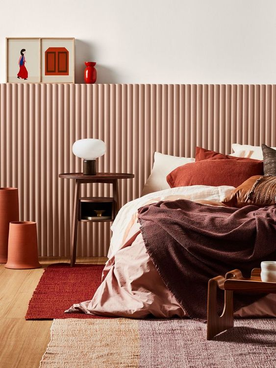 a bold fall-colored bedroom done with a palette of chocolate brown, rust, burgundy and deep red