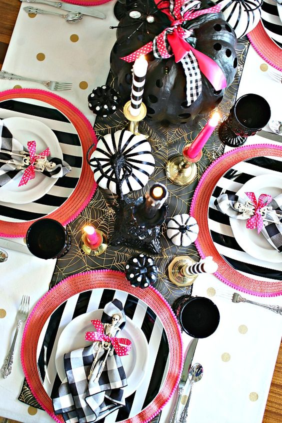 a bold modern Halloween tablescape with hot pink touches, black, white and gold and painted pumpkins