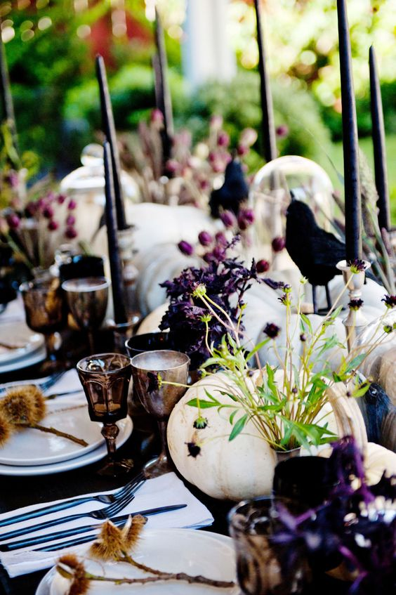 a bright and chic Halloween tablescape with white pumpkins, purple blooms, greenery, black candles, crows, dried grasses and goblets