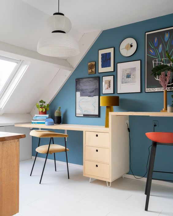 a bright attic home office with a blue accent wall, a desk with two different desktops, upholstered chairs and stools and a chic gallery wall