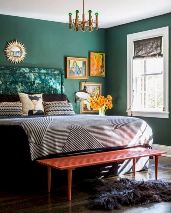 a bright fall bedroom done in emerald, with bright artworks, a red bench and metallics