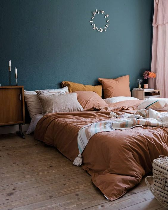 a bright fall bedroom with a dark green wall, rust and orange bedding and touches of stained wood