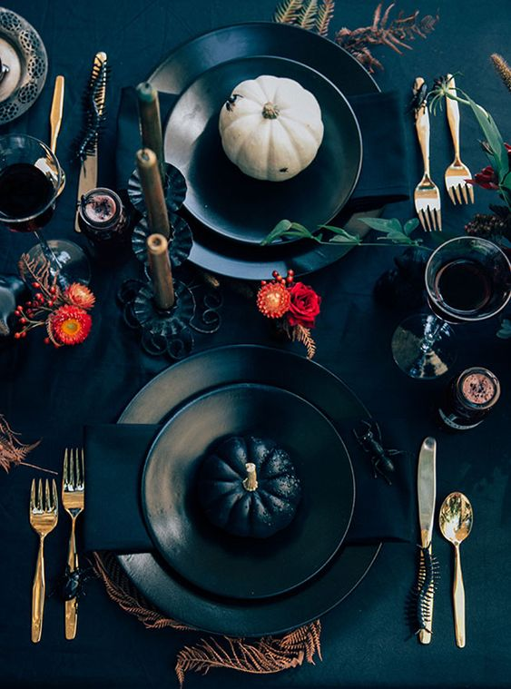 a bright modern Halloween tablescape with red blooms, spiders and snakes, gold cutlery, white and black pumpkins