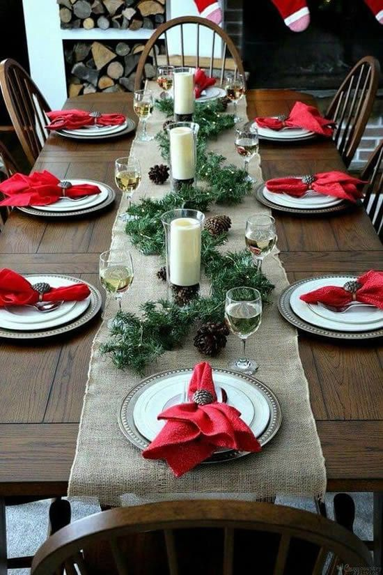 a bright winter tablescape with a burlap runner, red napkins, a pinecone and evergreen runner plus candles