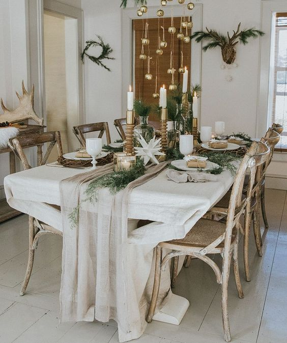 a chic and neutral winter tablescape with a neutral runner, greenery, paper stars candles in various candleholders and ornaments hanging over the table