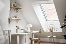 a chic attic home office with a white desk and neutral chair, some shelves, a tall stool and some dried blooms on a stand