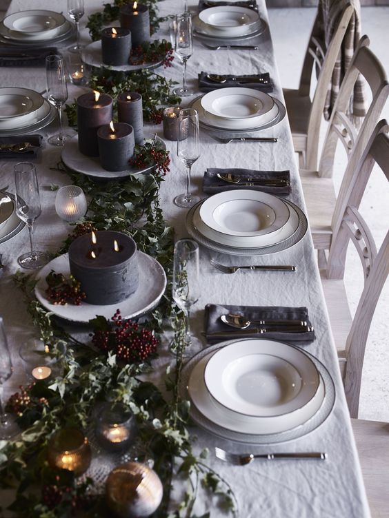 a chic dark tone winter tablescape with dark candles, greenery, berries, grey napkins and white porcelain