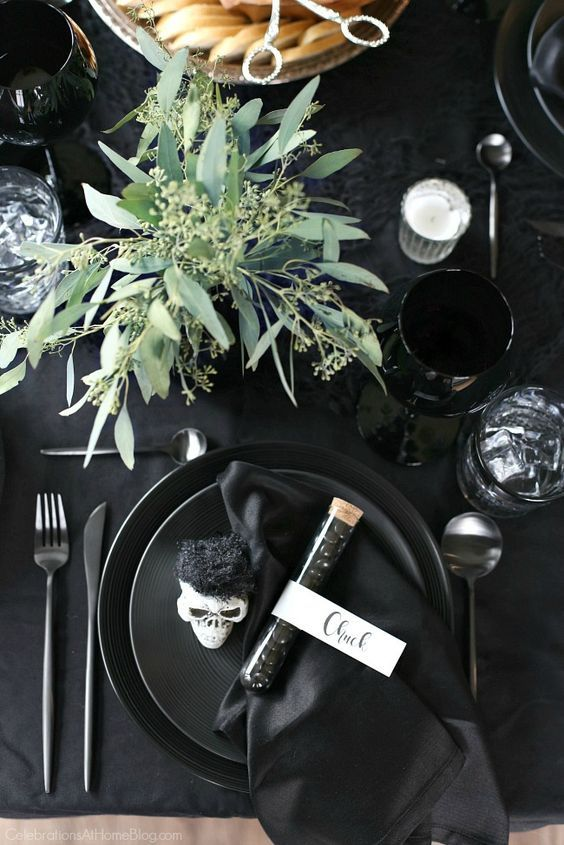 a classy modern Halloween tablescape with all things black, skulls, candies, eucalyptus, candles and matte cutlery