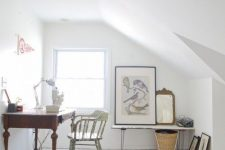 a clean and airy white attic home office with a planked floor, a vintage dark stained desk, a vintage chair, a bench, some artworks and a basket