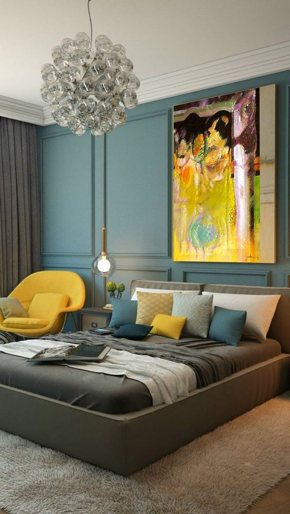 a colorful fall bedroom with a bright artwork, a yellow chair and pillow and lots of teal