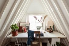 a cool attic home office with a desk by the window, a vintage chair and a reclaimed wood floor, potted greenery and artworks