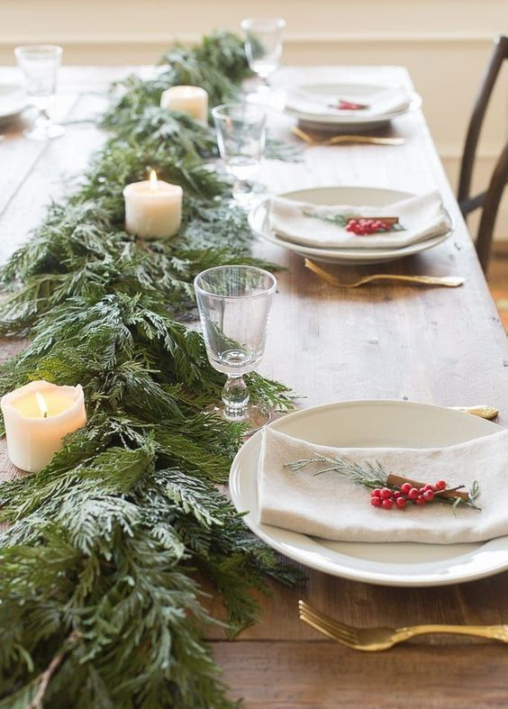 a cozy and homey winter table with an evergreen and pilalr candle runner, berries and evergreens plus gold cutlery