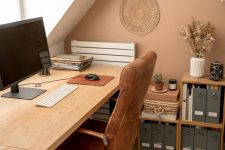 a cozy warm-colored home office with a comfy desk, an upholstered chair, bookshelves, decorative plates, a pendant woven lamp