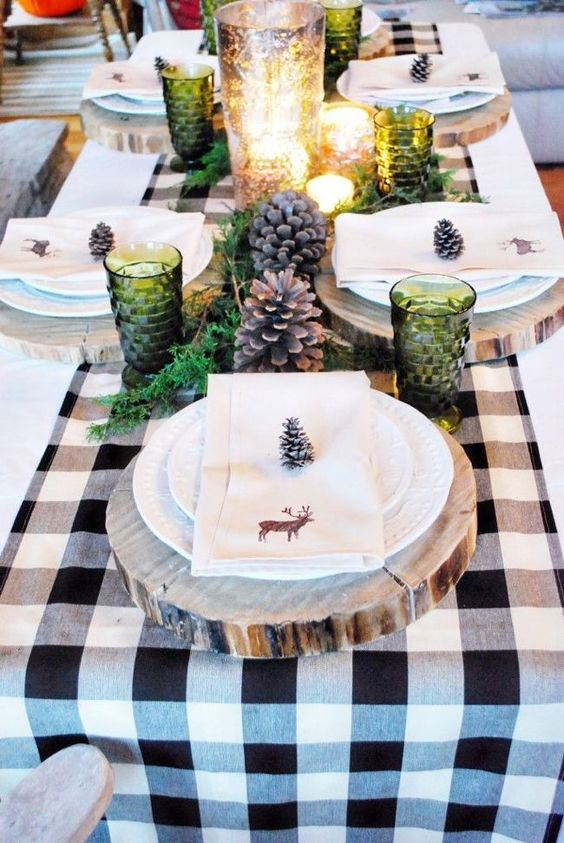a cozy winter table with a plaid runner, wood slice placemats, large pinecones, green glasses and lots of candles