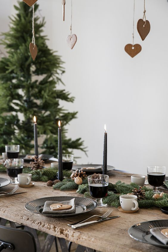 a cozy winter table with an evergreen, pinecone and nut runner, black candles and black plates plus gingerbread cookies over the table