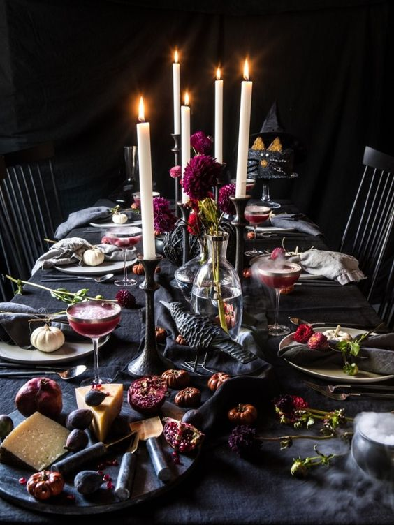 a decadent Halloween tablescape with black linens, crows, bold purple blooms, candles and dried flowers