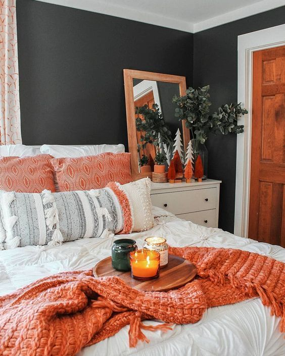 a fall colored bedroom done in black and white, with orange touches and greenery