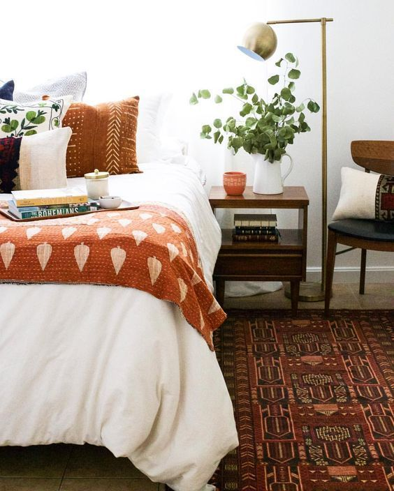 a fall colored bedroom with rust and orange textiles, a burgundy rug and some chocolate brown here and there
