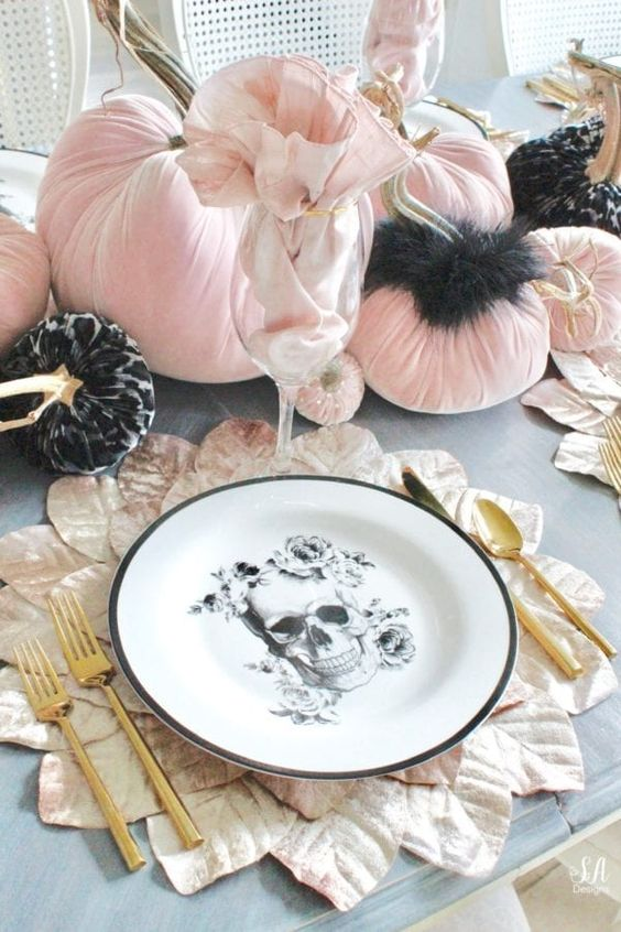 a glam Halloween table setting with black and pink velvet pumpkins, a skull plate, gold cutlery and leafy placemats