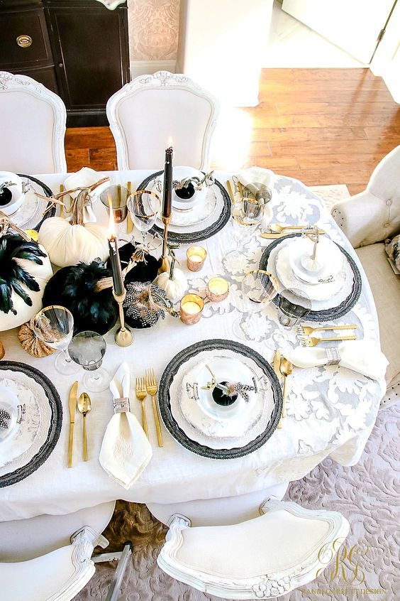 a glam Halloween tablescape with white and black pumpkins, black feathers, candles, gold cutlery and black chargers