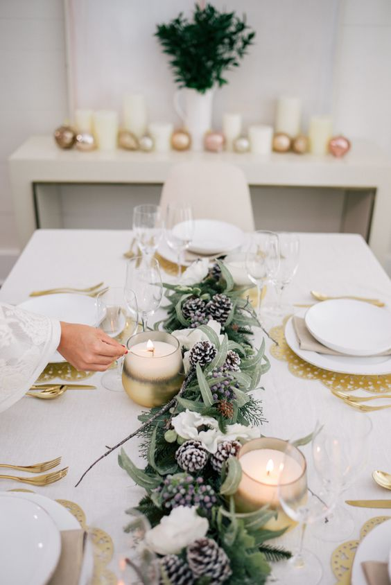a glam winter tablescape with gold placemats, an evergreen, white bloom and snowy pinecone runner, candles and gold cutlery