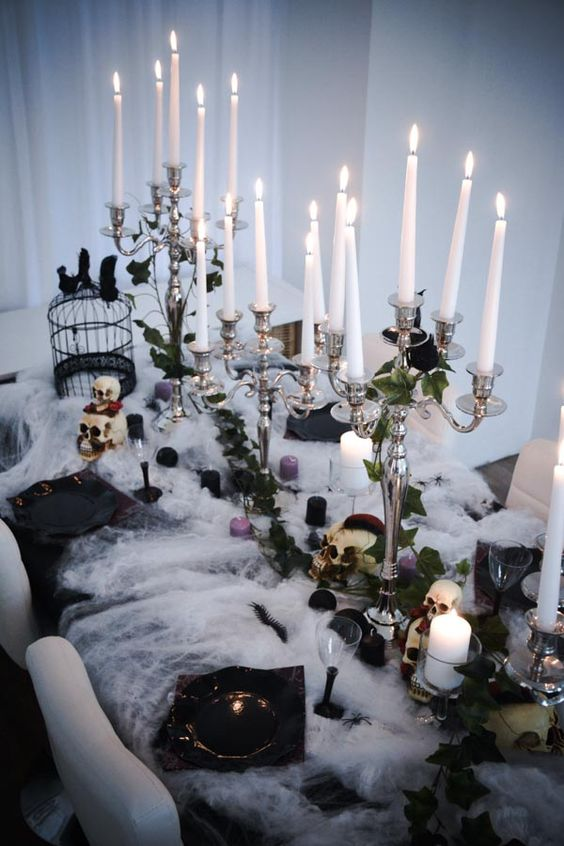 a gorgeous Halloween tablescape with black, purple and white candles, greenery, roses, black porcelain, crows and skulls