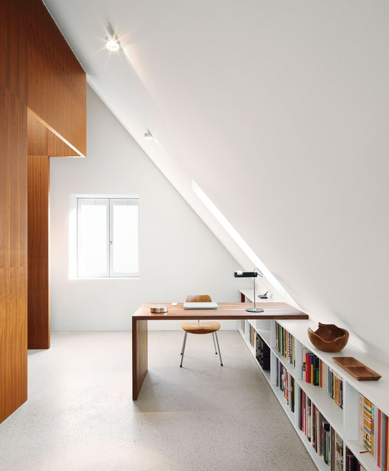 a minimalist attic home office with a long bookshelf and a built in desk, a chic table lamp and a comfy leather chair is filled with light and chic