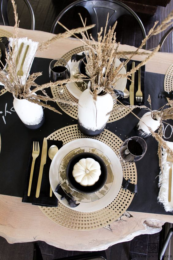 a modern glam Halloween table setting with gold chargers, cutlery, a black runner and watercolor vases with wheat